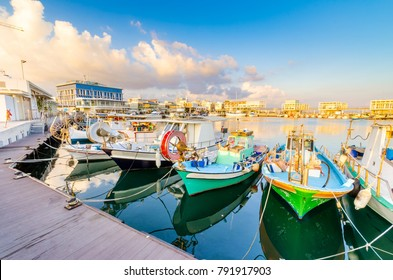 Fishing boats docked at the Limassol old port (palaio limani) in Cyprus, next to the Marina. The harbor, the mediterranean sea, the water, boat fish nets, equipment, restaurants and shops at sunset.