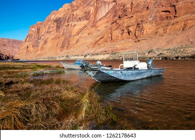 Fishing boats docked on the shore of Colorado river with towering red rock canyon walls looming near Lees Ferry AZ