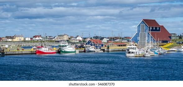 Fishing boats at docks in the villages' harbours in Bonavista, Newfoundland, Canada.   Newfoundland fishing villages see boats at rest for the day on calm coastal water.