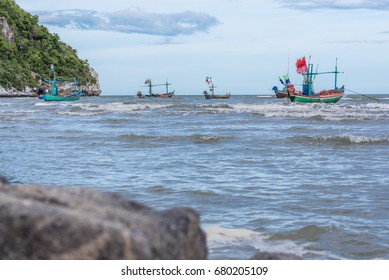 Fishing boats are floating on the sea at a village of fishermen where the big mountains at background / Sea scape