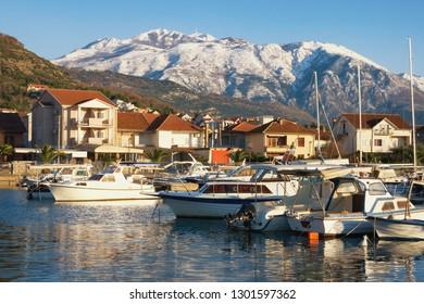 Fishing boats in harbor on background of snowy mountain peaks. Montenegro, Bay of Kotor. View of Marina Kalimanj in Tivat city and snow-capped of Lovcen mountains