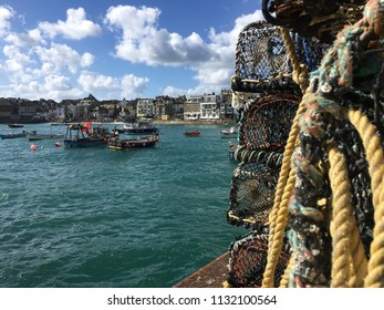 Fishing boats, high tide and lobster pots in St Ives Harbour, Cornwall JULY 2018