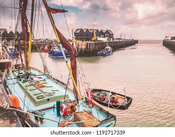 Fishing boats and huts in Whitstable harbour, Kent, UK. A small wooden rowing  boat can be seen hanging off the side on the Thames barge in the foreground.