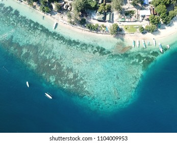 Fishing boats line the shores of Gili Air, Lombok, Indonesia. From above you have a clear view of the beautiful coral reefs and soft, white sand.
