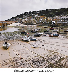Fishing boats, at low tide, in the Cornish fishing village of Mousehole.