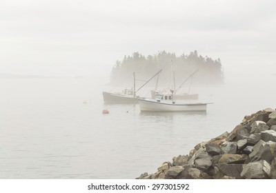 Fishing boats moored in Lubec Narrows near Bay of Fundy of Coastal Maine with thick fog beginning to lift.