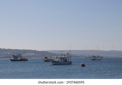 fishing boats moored in the mediterranean sea and hills, houses, forest and wind farms in the background. Concept of tranquility