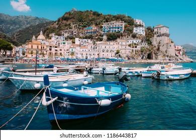 Fishing boats moored near Cetara with the town on the background, Camapania, Amalfi coast, Italy.