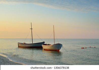 Fishing boats moored near the shore at sunset background