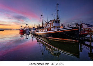 Fishing boats moored on the river creating reflections on the clear water, pastel coloured sunset on the horizon