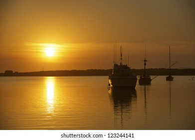 Fishing boats moored in still bay water during a warm sunset