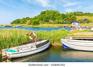 Fishing boats mooring in Baabe port and view of Moritzdorf village with houses on lake shore, Ruegen island, Baltic Sea, Germany