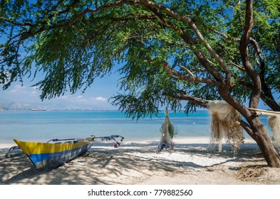fishing boats an nets on areia branca tropical beach in dili east timor leste