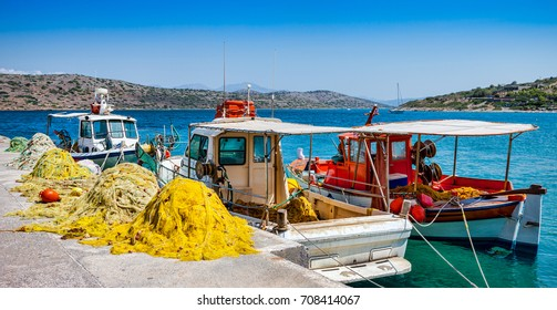 Fishing boats with nets at the pier in the village of Plaka in Crete, Greece