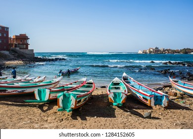 Fishing boats in Ngor Dakar, Senegal, called pirogue or piragua or piraga. Colorful boats used by fishermen standing in the bay of Ngor on a sunny day.