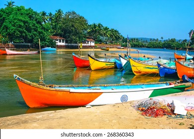 fishing boats on the beach  in tropical with palms, huts and blue sky. Goa, India