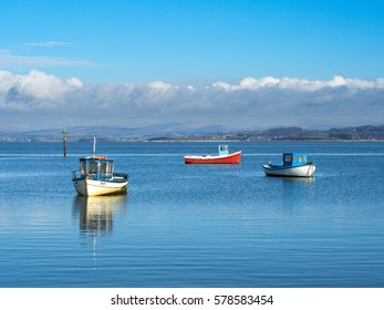 Fishing boats on calm sea at Morecambe Bay Lancashire England with distant view of bank of cloud and hills