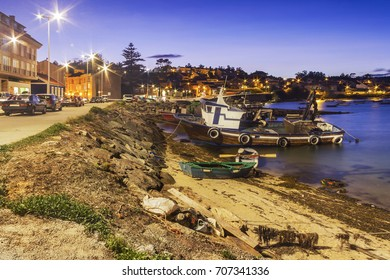 Fishing boats on Naval seafront and boardwalk in Arousa Island at night
