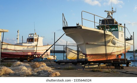 fishing boats on the shore under repair. large industrial fishing nets and ships in the port on the shore.
