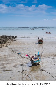 Fishing boats parked on the mud at low tide. By the beautiful sea and sky in the background.Thailand