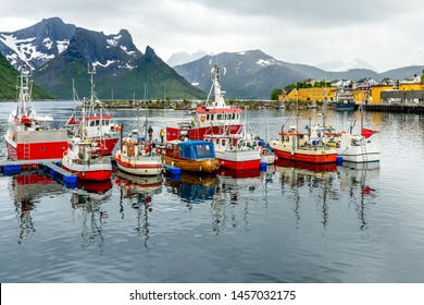 Fishing boats at the pier with mountain in the background at Husoy village, Senja island, Norway