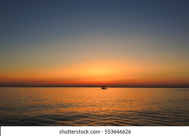 Fishing boats pull their nets at the sunrise. Adriatic cost. Emilia Romagna. Italy.