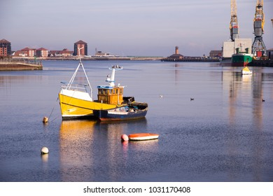 Fishing boats in the river Wear with the Port of Sunderland in the background reflected on to the waters on a calm day