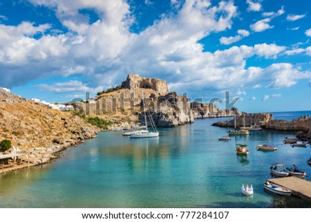 Fishing boats and sail boats in St. Paul´s bay, Lindos acropolis in background (Rhodes, Greece)
