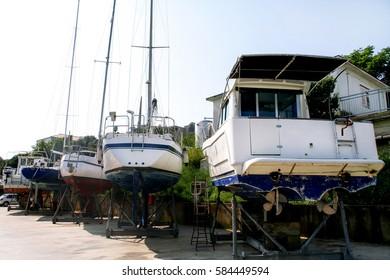 Fishing boats and sailboats at maintenance in the harbor and marina. Yachting concept.