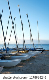 Fishing boats with sails down parked in line on the beach with peaceful ocean in the background and sunlight on the sand