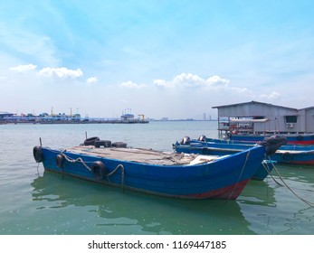 Fishing boats/ sampan parked along the Chew Jetty fishing village in Penang on a cloudy day