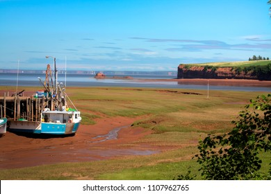 Fishing boats sit on the ocean floor during low tide. The tide rises and falls 50 feet in the Minas Basin of Nova Scotia, flooding the bay and allowing the boats to go to sea.