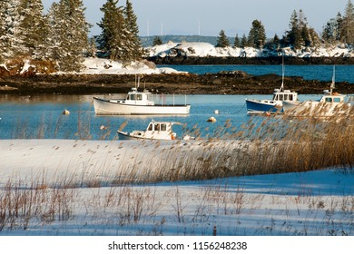 Fishing boats stay safe in snow covered Owls Head Harbor after a snowstorm in mid coast Maine.