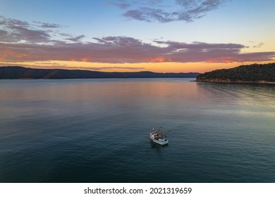 Fishing Boats and sunrise in Brisk Bay from Patonga Beach on the Central Coast of NSW, Australia.