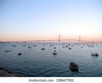 Fishing boats in sunset at the Puente de la Constitución, called La Pepa, in the bay of Cádiz, Andalusia. Spain