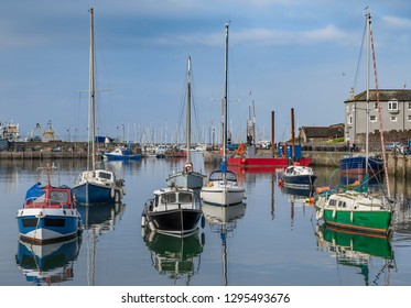 Fishing boats and Trawlers in Brixham, Torbay, Devon, UK. Sailing boats and yachts in the inner harbour with the tops of more sailing yachts and trawlers in the background.