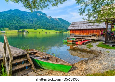 Fishing boats and wooden house on shore of Weissensee lake in summer landscape of Carinthia land, Austria