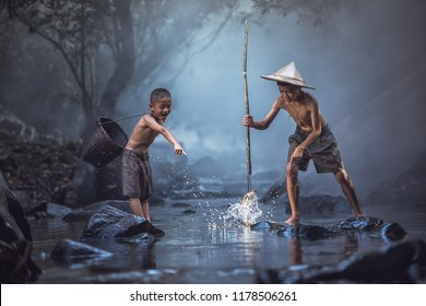 Fishing boys fishing in the river, countryside of Thailand.