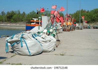 Fishing buoys and bags with fishing net on quay in small harbour