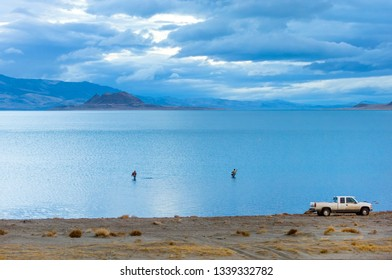 Fishing in calm waters of Pyramid lake in early morning, Nevada, USA
