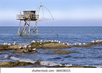Fishing carrelet with the seagulls on the rocks at Saint-Michel-Chef-Chef in the Loire-Atlantique department in western France.