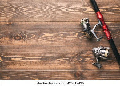 Fishing concept. Fishing spinning rod and reels with lines on wooden background with free space.