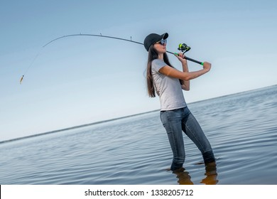 Fishing concept. Young fisherwoman makes a cast on background of skewed horizon line