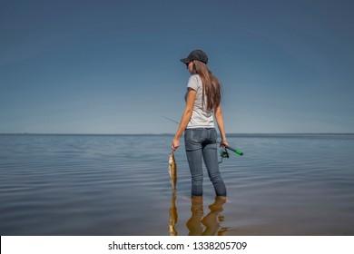 Fishing concept. Young fisherwoman with tackles and walleye zander fish at lake coast