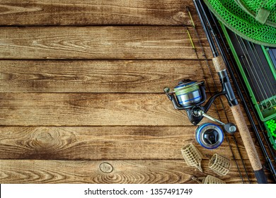 Fishing feeder and reel.Fishing tackle background.Fishing feeder- hooks and lures on darken wooden background.