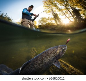 Fishing. Fisherman and trout, underwater view.
