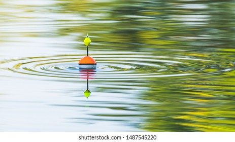 A fishing float floats on the water of the lake making circles in the water