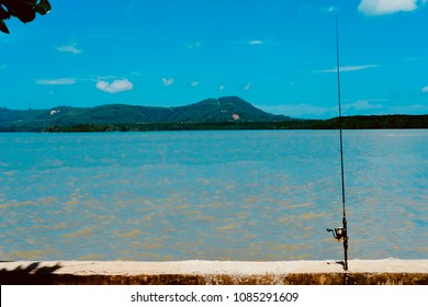 Fishing gear is placed by the sea. Waiting for the fish to eat the bait Behind the sea is the mountain and the beautiful sky.