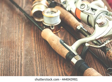 Fishing gear - fishing spinning, fishing line, hooks and lures on wooden background. Toned image