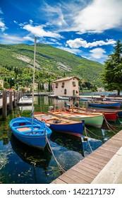 fishing harbor with colorful boats in Nago-Torbole, Garda lake, Trentino-Alto Adige region, Italy